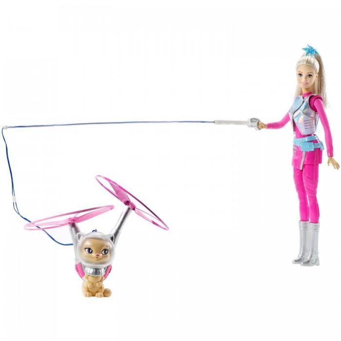 Barbie Кукла Барби с летающим котом ПопкорномКукла Барби с летающим котом ПопкорномКукла Барби с летающим котом Попкорном «Barbie и космические приключения» увлечет вашего ребенка очень надолго.   Барби одета в розово-серебристый космический костюм с широким голубым поясом.  Поверх костюма надет серебристый жилет.  Дополняют наряд длинные серебристые сапоги.  Светлые длинные волосы куклы аккуратно убраны в высокий хвост.  Бежевый котик в серебристом не снимаемом шлеме действительно умеет летать.  Если прикрепить поводок (входит в комплект) к руке куклы и нажать кнопку на ее ноге, то розовые пропеллеры закрутятся и кот полетит.   Игровой набор продается в красочной блистерной упаковке.   Рекомендуемый возраст: от 3 лет.<br>