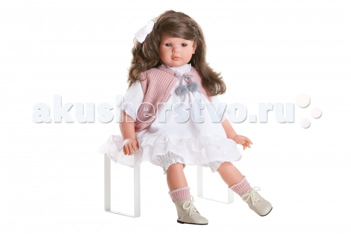 Dnenes/Carmen Gonzalez Кукла Даниэла в воздушном платье и розовом жилете 60 смКукла Даниэла в воздушном платье и розовом жилете 60 смКукла Даниэла в воздушном платье и розовом жилете - большая и привлекательная кукла-девочка испанского производителя традиционных кукол для детей Dnenes.  Кукла Даниэла очень похожа на настоящую девочку. У неё выразительное лицо и глубокий взгляд, роскошные и длинными волосы.  Любая девочка будет в восторге от этой куклы. Кукла украсит самый изысканный интерьер.  Кукла выполнена в сидячей позе.  Даниэла одета в воздушное светлое платье и вязаную розовую жилетку. Платье имеет рукава до локтя с манжетами, декоративный воротничок-стоечку и застегивается сзади на пуговицы. Юбка выглядит длинной и пышной не только благодаря легкой ткани, но и фасону платья - оба яруса юбки начинаются от высокой кокетки на груди, а нижний ярус сшит из плотной хлопчатобумажной ткани, которая держит форму. Розовый жилет выглядит объемным за счет крупной вязки. Застегивается он на груди при помощи завязочек с трогательными помпончиками. В комплект входят белые панталончики. На ножках одеты розовые вязаные носочки и высокие бежевые ботиночки из натуральной кожи на шнуровке.  Глаза карие, стеклянные, обрамлены ресничками, не закрываются. Тело комбинированное: твердый винил, мягко набивные вставки.  Кукла не имеет запаха и обладает приятным тактильным эффектом.  Коллекционная кукла Carmen Gonzalez продается в красивой подарочной коробке.<br>