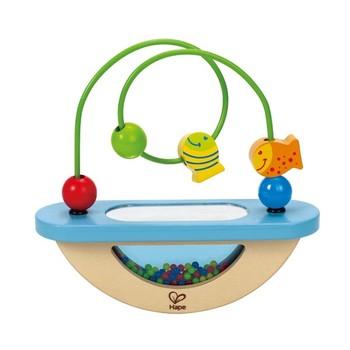 Деревянная игрушка Hape Развивающая игрушка-лабиринт Е0429Развивающая игрушка-лабиринт Е0429Передвигая забавные фигурки рыбок по проволоке, малыш тренирует мелкую моторику и координацию пальчиков.  В прозрачном основании находятся разноцветные бусинки, которые стимулируют развития координации зрения у ребенка, учат фокусировать зрение на мелких движущихся объектах.  Основание игрушки выполнено в форме качелей, что позволяет малышу понять принципы равновесия.<br>