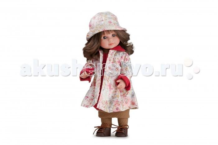 Dnenes/Carmen Gonzalez Кукла Мариэтта в цветочном плаще и шляпе 34 смКукла Мариэтта в цветочном плаще и шляпе 34 смОчень красивая кукла-девочка испанского производителя традиционных кукол для детей Dnenes. Высота куклы - 34 см.  Кукла одета в вишневую тунику из вельвета и плащ с очень красивым цветочным рисунком. Ворот и низ туники отделаны трикотажной резинкой горчичного цвета.  Плащ из непромокаемой прорезиненной ткани, отрезной по линии талии, имеет длинные рукава. Воротник и обшлага рукавов у плаща декорированы вишневой вельветовой тканью. В дополнение к плащу голову куклы украшает кокетливая шляпка из того же материала.  Рейтузы выполнены из рельефного трикотажа горчичного цвета. На ножках обуты аккуратные горчичные кожаные ботиночки со шнуровкой и перфорацией.  Тело - Твердый винил Волосы - Каштановые, волнистые, хорошо прошиты Глаза - Карие, стеклянные, обрамлены ресничками, не закрываются Одежда - Высококачественный текстиль. Вишневая туника и плащ с цветочным рисунком Головной убор - Кокетливая шляпка из прорезиненной ткани Детали - Трикотажные рейтузы Обувь - Кожаные ботиночки со шнуровкой Дизайн - Изысканный. Детали лица, рук и ножек великолепно проработаны.  Упаковка - Красивая подарочная коробка с прозрачным окошком.  Все куклы Carmen Gozalez производятся на заводе в Испании по классической технологии. Технология изготовления кукол из латекса или винила была внедрена в 1940 году, в 1950-х эта технология стала популярна среди известных кукольных брендов по всему миру. Все куклы изготавливаются по уникальным пресс-формам с применением ручного труда. Каждая кукла хранит в себе тепло рук мастера.  Компания Dnenes очень гордится качеством своих кукол, компания неоднократно получала престижные награды на международных выставках, имеет европейские сертификаты безопасности. К особенностям испанских кукол Carmen Gonzalez стоит отнести и тот факт, что куклы не имеют запаха, который многими производителями заглушается сильно пахнущими отдушками. Волосы у кукол име